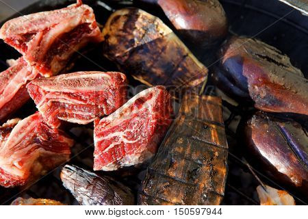 different kind of meat: chicken shish kebab, beef asado, beef fillet, with raw eggplant on black bbq grill grid prepared on charcoal