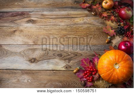 Thanksgiving or fall greeting background with pumpkins and fall leaves. Thanksgiving background with seasonal vegetables and fruits. Fall background. Copy space