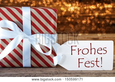 Macro Of Christmas Gift Or Present On Atmospheric Wooden Background. Card For Seasons Greetings, Best Wishes Or Congratulations. White Ribbon With Bow. German Text Frohes Fest Means Merry Christmas