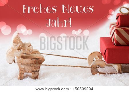 Moose Is Drawing A Sled With Red Gifts Or Presents In Snow. Christmas Card For Seasons Greetings. Red Christmassy Background With Bokeh Effect. German Text Frohes Neues Jahr Means Happy New Year