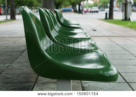 Empty Green Chair At The Public Bus Stop On The Footpath.