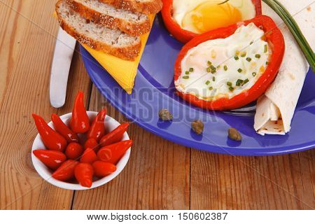 fried eggs and tortilla with salad , red hot pepper and mustard, served on blue plate with cutlery over wooden table in restaurant