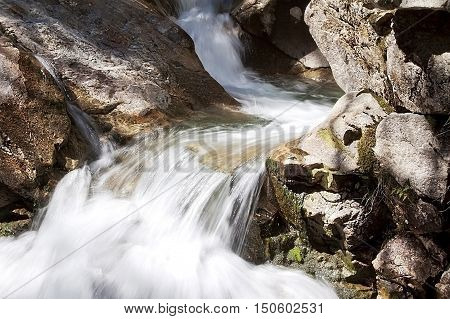 Close view of one of the small waterfalls at Franconia Notch NH on one of the many walking/hiking paths, on a bright, sunny day.