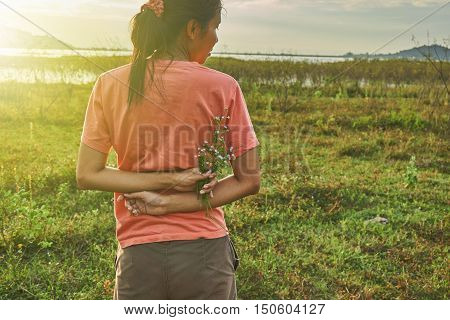 Young aisan woman standing with arms behind her back and hold the tiny flowers in her hand. A beautiful woman in rim light