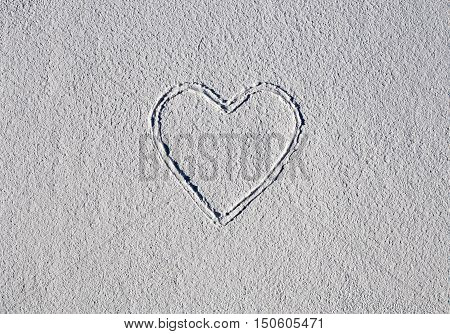 Heart on white structural plaster with paintbrush, copy space
