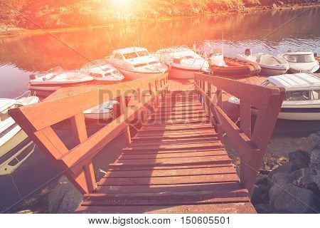 public beautiful harbor buil in old style by wood and light use for summer time. old port boat wood bridge transport. sunset background