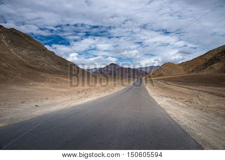 Road in mountains Himalayas and dramatic clouds on blue sky. Ladakh, Jammu and Kashmir, India.