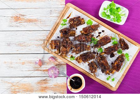 delicious hot sticky ribs seasoned with a spicy garlic ginger barbecue sauce and cilantro on parchment paper on chopping board. on table mat on white peeling paint planks view from above
