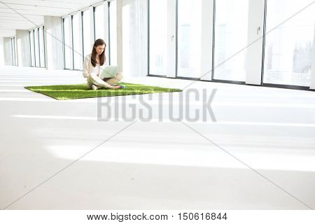 Young businesswoman using laptop while sitting on turf in empty office