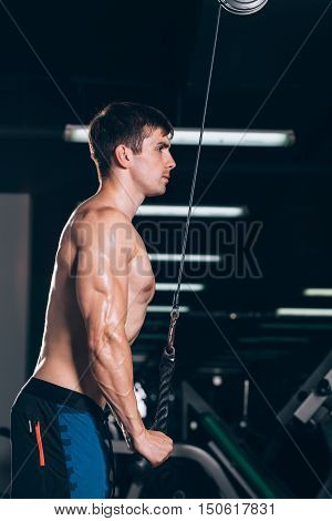 Muscular man working out in gym doing exercises at triceps, strong male naked torso abs.