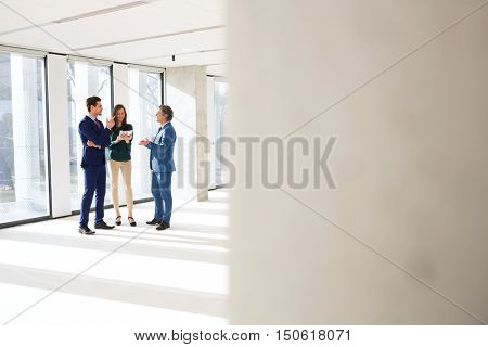 Full length of business people discussing in new office