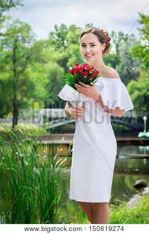 Portrait of happy beautiful smiling bride in white frilly dress whith open shoulders, holding wedding bouquet of red roses, standing in a park
