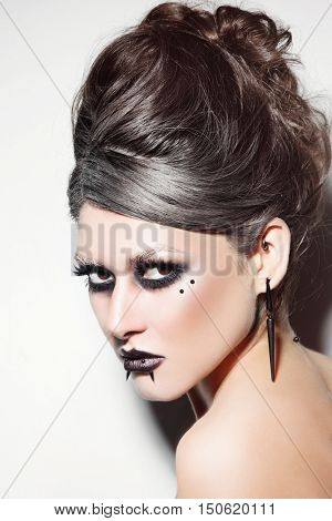 Portrait of young beautiful woman with facial piercings and stylish gothic make-up
