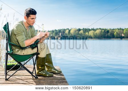 Man fishing at lake fixing lure at angling rod