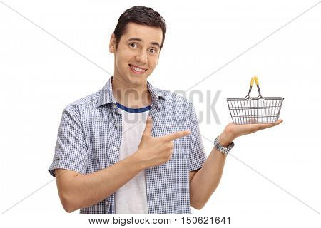 Joyful man holding a small empty shopping basket and pointing isolated on white background
