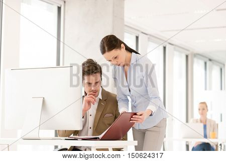Businesswoman and businessman reviewing file at computer desk in office