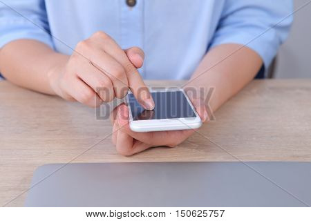 Business woman using and touchiing smartphone on wooden desk