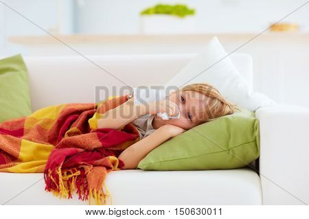 Sick Kid With Runny Nose And Fever Heat Lying On Couch At Home