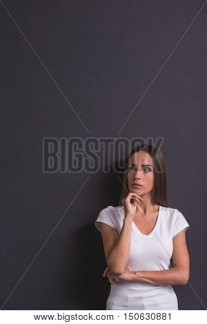 Beautiful young pensive girl in white t-shirt is looking away rubbing her chin and thinking standing against blackboard