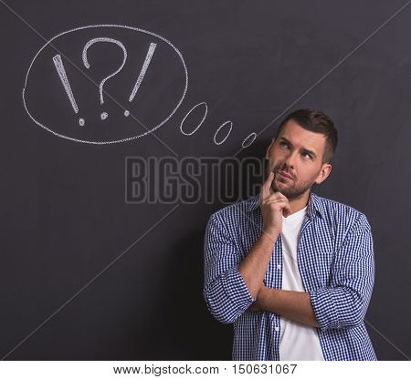 Handsome young pensive man is looking away rubbing his chin and thinking standing against blackboard with drawn speech bubble
