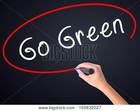 Woman Hand Writing Go Green With A Marker Over Transparent Board
