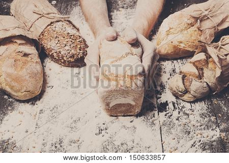 Lots of different bread sorts, wrapped in craft paper. Baking and cooking concept background. Hands of baker carefully hold loaf on wooden table, sprinkled with flour.