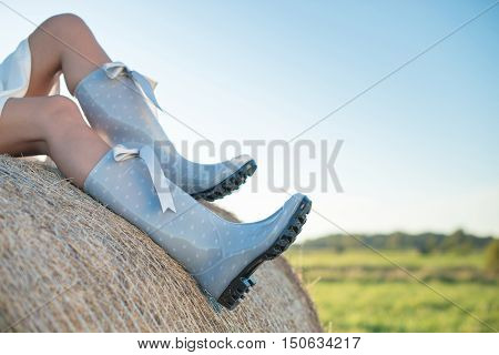 Girl In Rain Boots Sitting On The Haystack In The Field