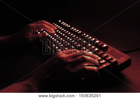 illuminated keyboard. male hands typing on a computer. hacker or programmer at work. on a black background. red tint.