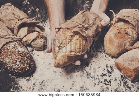 Lots of different bread sorts, wrapped in craft paper. Baking and cooking concept background. Hands carefully hold loaf on wooden table, sprinkled with flour. Soft toning