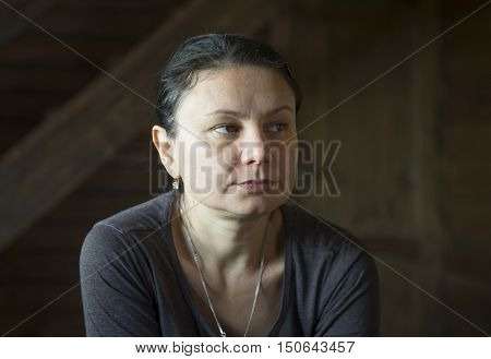 Low key portrait of a tired mature woman at home