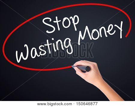 Woman Hand Writing Stop Wasting Money With A Marker Over Transparent Board