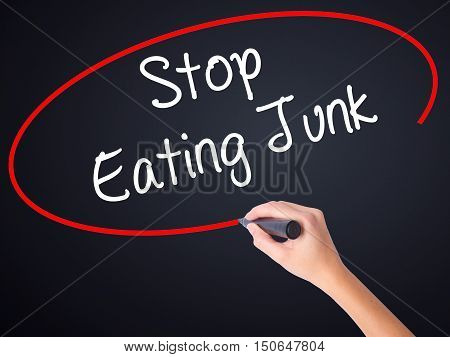 Woman Hand Writing Stop Eating Junk With A Marker Over Transparent Board .