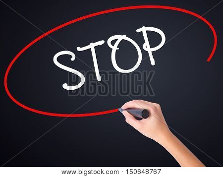 Woman Hand Writing Stop With A Marker Over Transparent Board .
