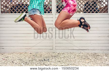 Low section of two unrecognizable women jumping over white garden fence background