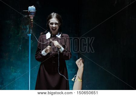 Portrait of a young girl with knife and drop counter in school uniform as killer woman against school board . The image in the style of Halloween and Addams family