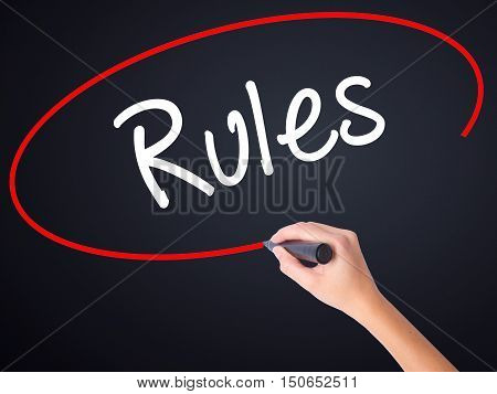 Woman Hand Writing Rules With A Marker Over Transparent Board .