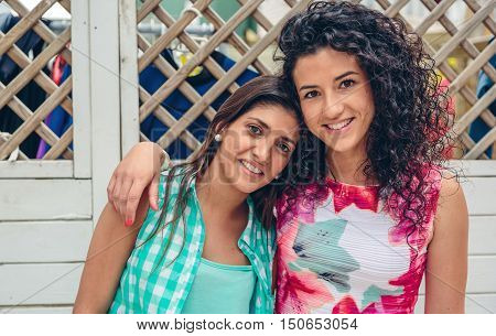Portrait of two happy young women looking at camera over white garden fence background