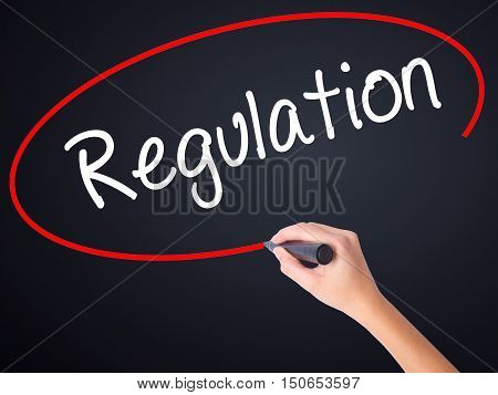 Woman Hand Writing Regulation  With A Marker Over Transparent Board