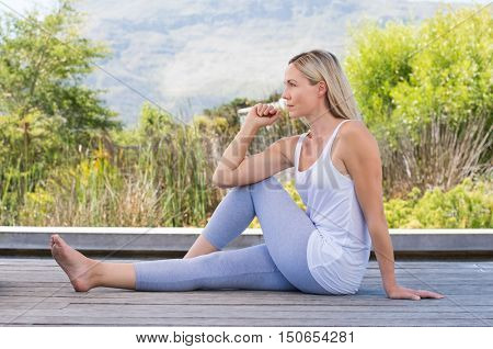 Smiling senior woman stretching and exercising outdoor. Senior relaxed woman doing yoga stretches after exercise. Beautiful woman relaxing with yoga pose.
