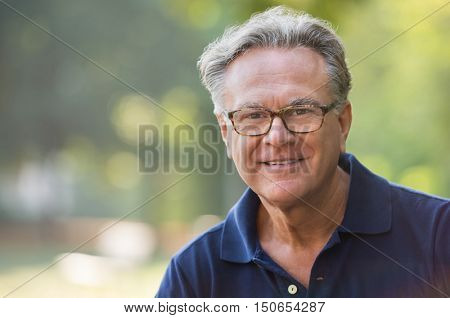 Portrait of senior man smiling and loooking at camera. Face of a happy old man wearing eyeglasses outdoor. Retired man with grey hair relaxing at park during morning.