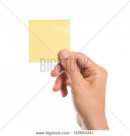 Male hand holding a yellow empty sticky note isolated on white background. Man hand holding blank yellow notepaper on white background. Close up of hand showing square post it.
