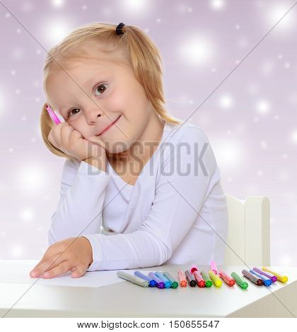 The concept of celebrating the New year, Holy Christmas, or child's birthday on a purple background and white snowflakes.Pretty little blonde girl drawing with markers at the table.