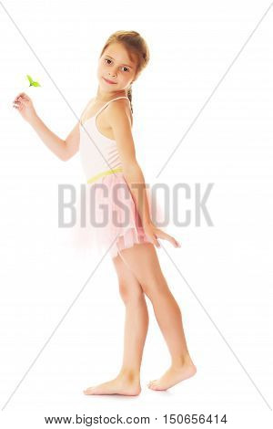Adorable little girl in pink ballerina dress, turning sideways to the camera , holding a green stem with leaves.Isolated on white.