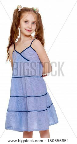 Adorable little girl with long pigtails to her waist and braided white bows. In a long blue dress. Standing sideways to the camera. Close-up - Isolated on white background