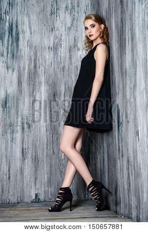 Fashion shot of a beautiful female model posing at studio. Beauty, fashion. Make-up, hairstyle.
