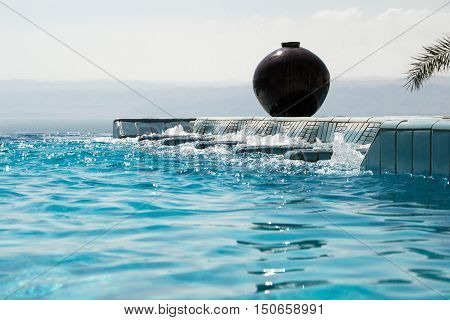 Photo of the Infinity pool jacuzzi with azure water. Luxury lifestyle, recreation concept.