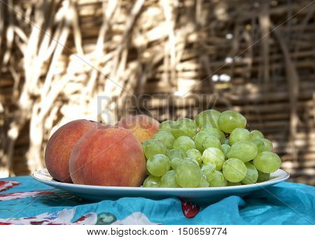French peaches and grapes prepared on a table in natural blurry background, maltese fruits. Fresh fruits peaches and grapes on a table. Fruits cocktail