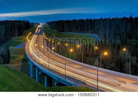 Night lighting a road overpass in the woods.