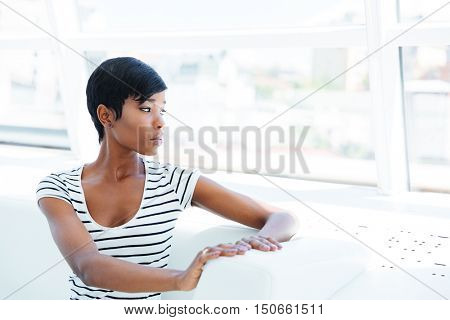 Serious african american young woman accountant sitting in office