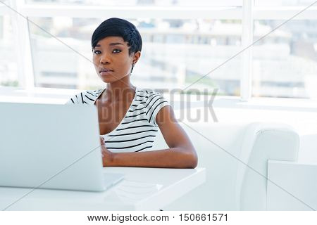 Portrait of a casual young african businesswoman using laptop computer in office
